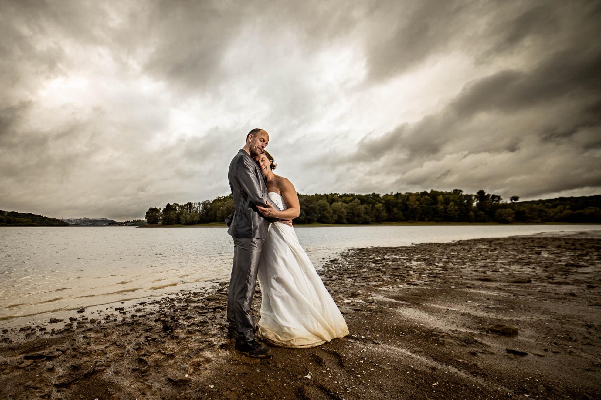 Mariés posant devant un lac sous les nuages