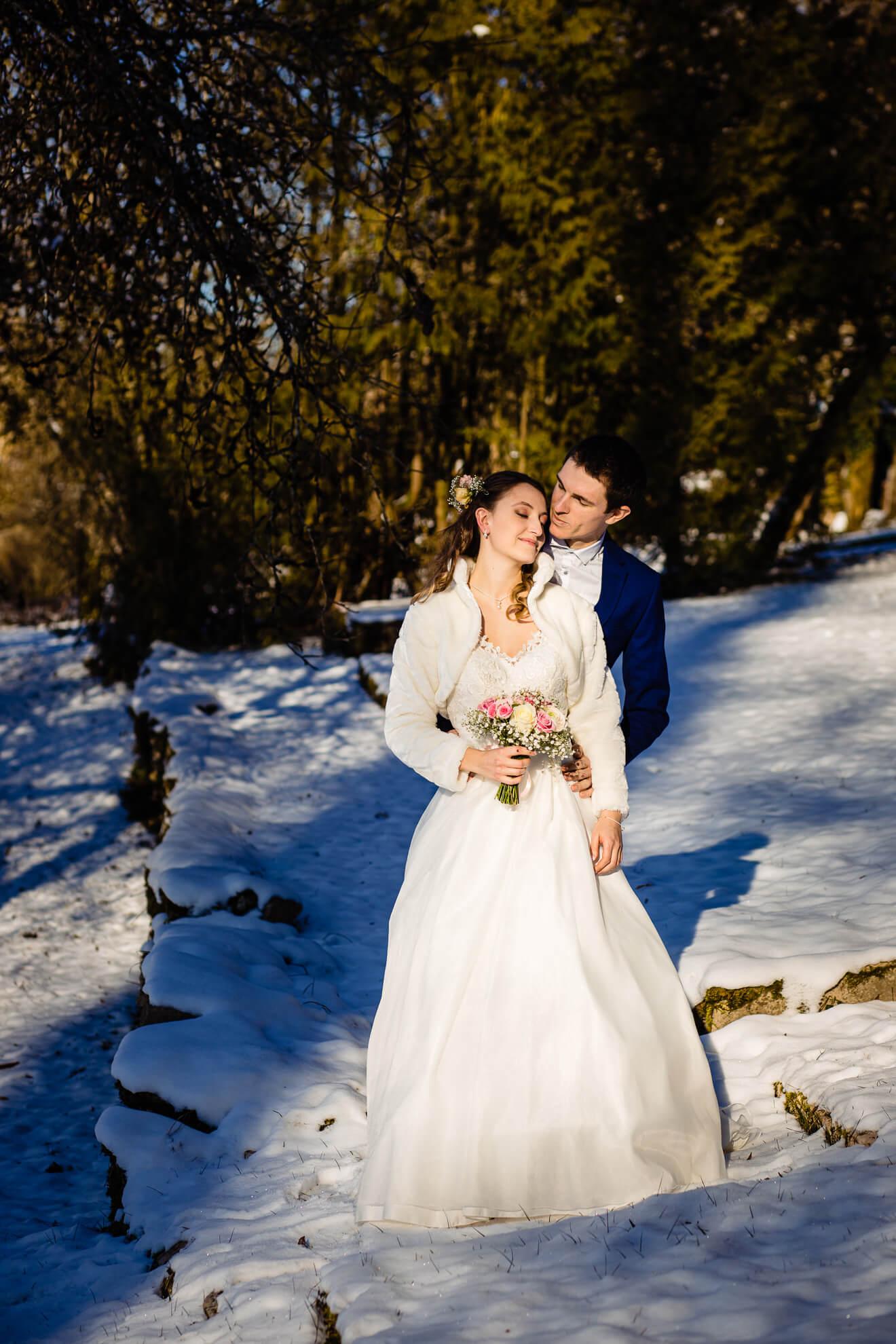 Jeunes mariés posant dans un jardin enneigé