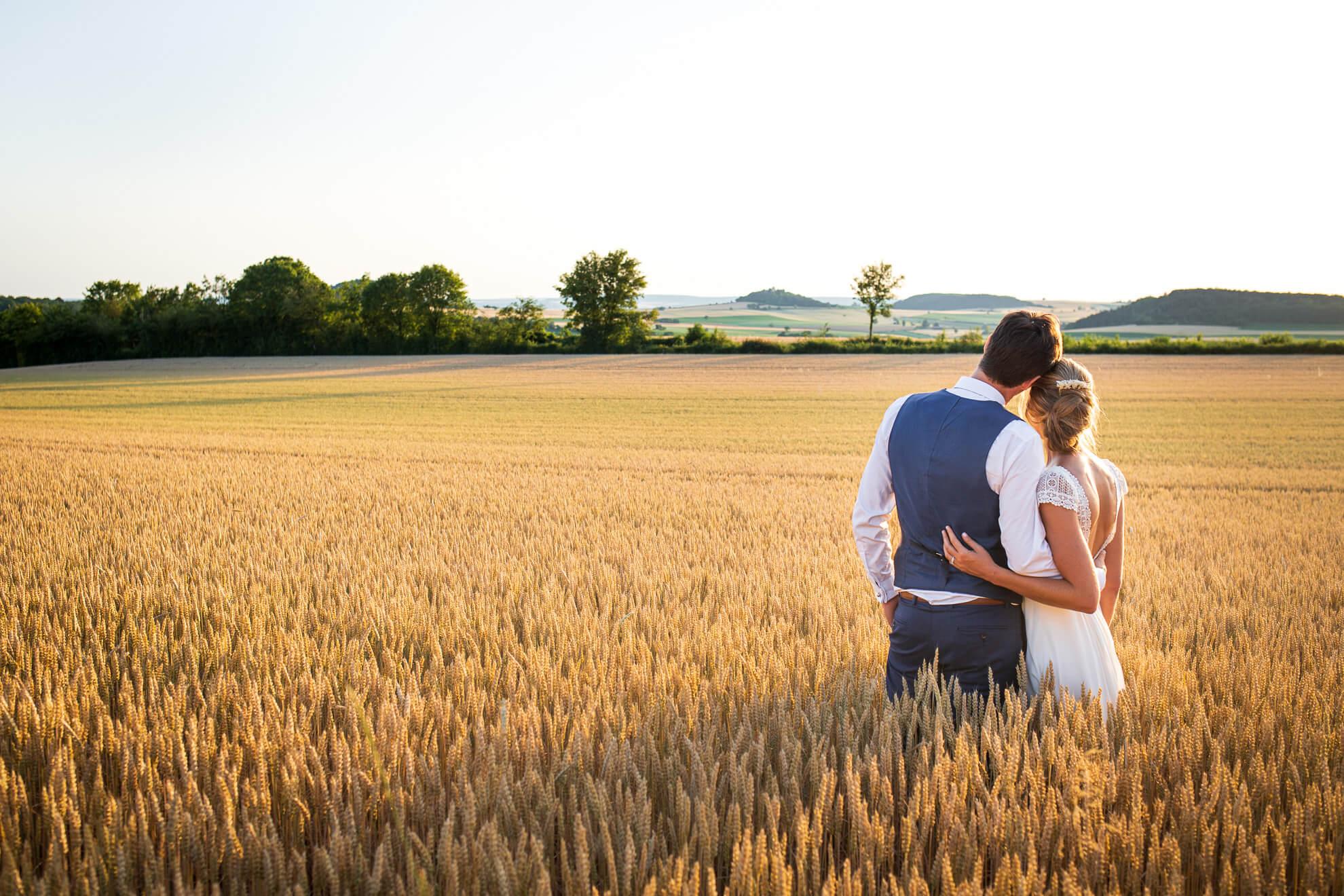 Mariés dans le champ au soleil couchant
