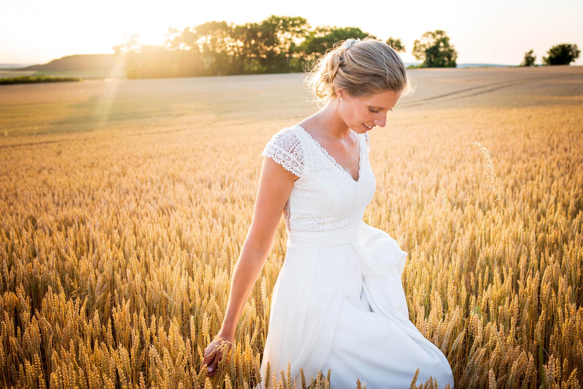 Mariée marchant dans les blés au soleil couchant